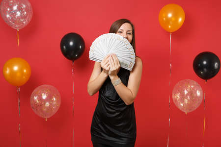 Young girl in black dress hiding, covering face with bundle lots of dollars, cash money in hand on bright red background air balloons. Women's Day Happy New Year birthday mockup holiday party concept