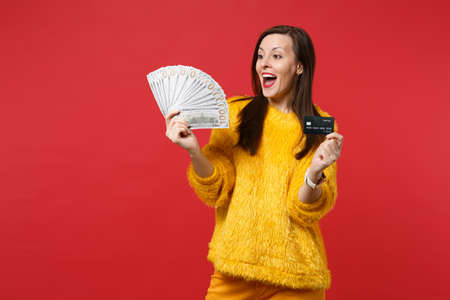 Excited girl keeping mouth wide open, holding credit bank card, fan of money in dollar banknotes, cash money isolated on red background. People sincere emotions, lifestyle concept. Mock up copy space