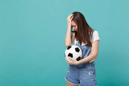 Disappointed woman football fan support favorite team with soccer ball putting hand on lowered head isolated on blue turquoise wall background in studio. People emotions, sport family leisure concept