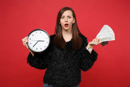Bewildered young woman in black fur sweater holding round clock fan of money in dollar banknotes cash money isolated on red background. People sincere emotions, lifestyle concept. Time is running out