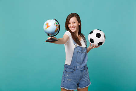Pretty young woman football fan support favorite team with soccer ball, world globe isolated on blue turquoise background. People emotions, sport family leisure lifestyle concept. Mock up copy space Imagens