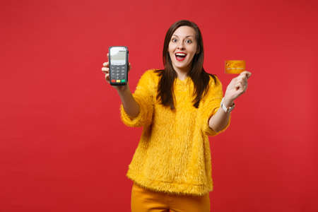 Surprised young woman in yellow fur sweater hold wireless modern bank payment terminal to process, acquire credit card payments isolated on red background. People sincere emotions, lifestyle concept