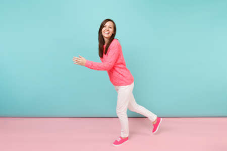 Full length portrait of smiling young woman in knitted rose sweater, white pants posing isolated on bright pink blue pastel wall background in studio. Fashion lifestyle concept. Mock up copy space 写真素材