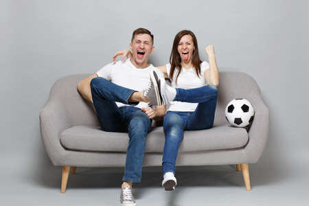 Cheerful couple woman man football fans cheer up support favorite team with soccer ball clenching fist, showing tongue isolated on grey wall background. People sport family leisure lifestyle concept Stock Photo