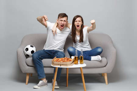 Irritated screaming couple woman man football fans in white t-shirt cheer up support favorite team and showing thumbs down isolated on grey background. People emotions, sport family lifestyle concept