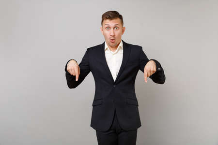 Shocked young business man in classic black suit pointing index fingers down, looking surprised isolated on grey background in studio. Achievement career wealth business concept. Mock up copy space