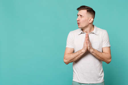 Portrait of praying young man in casual clothes looking aside and folded his hands isolated on blue turquoise wall background in studio. People sincere emotions, lifestyle concept. Mock up copy space Imagens