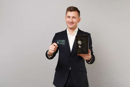 Successful young business man in classic suit hold credit bank card, metal bank safe for money accumulation isolated on grey background. Achievement career wealth business concept. Mock up copy space