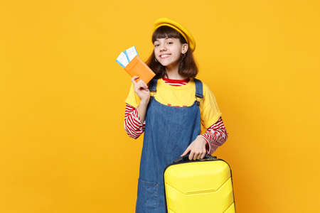 Beautiful girl teenager in french beret denim sundress holding suitcase passport boarding pass ticket isolated on yellow wall background. People sincere emotions lifestyle concept. Mock up copy space