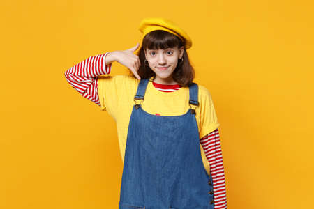 Bright girl teenager in french beret, denim sundress doing phone gesture like says call me back isolated on yellow background in studio. People sincere emotions, lifestyle concept. Mock up copy space