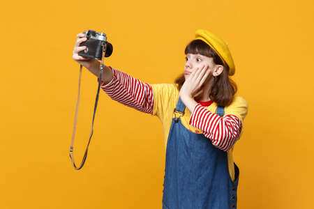 Perplexed girl teenager in french beret doing selfie shot on retro vintage photo camera, put hand on face isolated on yellow background. People sincere emotions, lifestyle concept. Mock up copy space