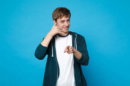 Smiling man in casual clothes doing phone gesture like says call me back, pointing index finger on camera isolated on blue background. People sincere emotions, lifestyle concept. Mock up copy space