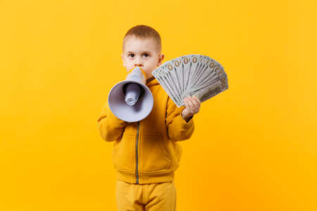 Little happy kid boy in yellow clothes hold fan of money in dollar banknotes, megaphone isolated on orange wall background, children studio portrait. Childhood lifestyle concept. Mock up copy space 版權商用圖片
