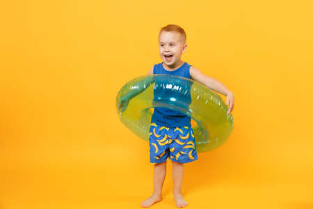 Kid boy 3-4 years old in blue beach summer clothes hold inflatable ring isolated on bright yellow orange background children studio portrait. People childhood lifestyle concept Mock up copy space