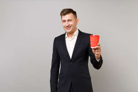Smiling young business man in classic black suit, shirt holding paper cup with coffee or tea isolated on grey wall background in studio. Achievement career wealth business concept. Mock up copy space
