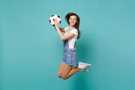 Smiling girl football fan cheer up support favorite team holding soccer ball jumping isolated on blue turquoise background. People emotions, sport family leisure lifestyle concept. Mock up copy space Archivio Fotografico