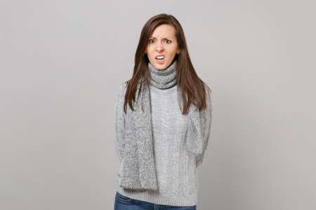 Preoccupied young woman in gray sweater, scarf holding hands behind her back isolated on grey background. Healthy fashion lifestyle, people sincere emotions, cold season concept. Mock up copy space Foto de archivo