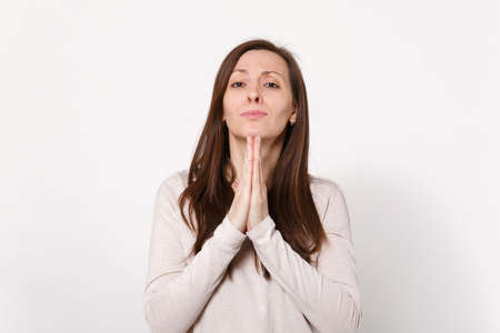 Portrait of pleading concerned young woman in light clothes holding hands together, praying isolated on white wall background in studio. People sincere emotions, lifestyle concept. Mock up copy space 写真素材