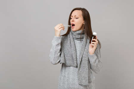 Sick young woman in gray sweater, scarf holding pour liquid medicine into spoon isolated on grey wall background. Healthy lifestyle ill sick disease treatment, cold season concept. Mock up copy space