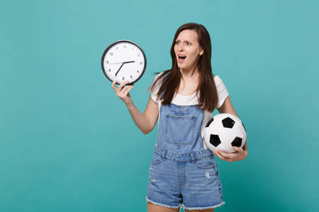 Irritated young woman football fan holding soccer ball, round clock isolated on blue turquoise wall background in studio. Time is running out. People emotions, sport family leisure lifestyle concept