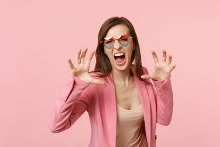 Crazy young woman in heart glasses shouting growling like animal, making cat claws gesture isolated on pastel pink background in studio. People sincere emotions, lifestyle concept. Mock up copy space Stockfoto