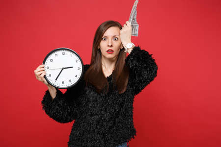 Shocked concerned woman in black fur sweater hold round clock, fan of money in dollar banknotes, cash money isolated on red background. People sincere emotions, lifestyle concept. Time is running out