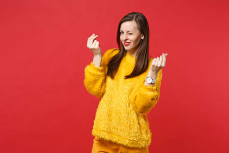 Tricky young woman in yellow fur sweater blinking, rubbing fingers, showing cash gesture, asking for money isolated on red background. People sincere emotions, lifestyle concept. Mock up copy space Stock Photo