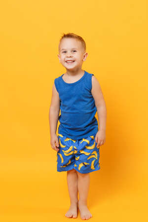 Little cute kid boy 3-4 years old wearing blue beach summer clothes isolated on bright yellow orange wall background, children studio portrait. People, childhood lifestyle concept. Mock up copy space