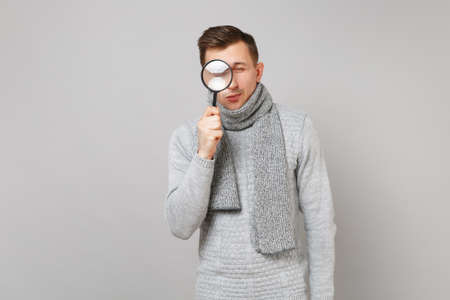 Young man in gray sweater, scarf holding, looking behing magnifying glass isolated on grey wall background. Healthy fashion lifestyle, people sincere emotions cold season concept. Mock up copy space Stock fotó