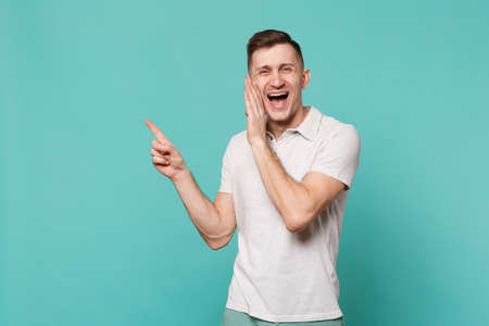 Laughing young man in casual clothes pointing index finger aside tells something with hand gesture isolated on blue turquoise background. People sincere emotions lifestyle concept. Mock up copy space