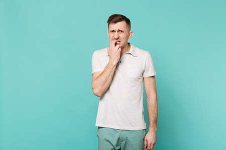 Portrait of disturbed worried young man in casual clothes gnawing nails, fingers isolated on blue turquoise wall background in studio. People sincere emotions, lifestyle concept. Mock up copy space Imagens