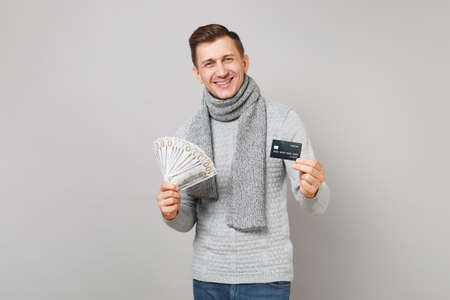 Laughing young man in gray sweater, scarf hold lots bunch of dollars banknotes, cash money, credit bank card isolated on grey background. Healthy lifestyle people sincere emotions cold season concept 写真素材