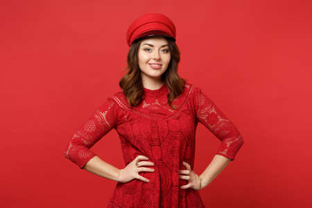 Portrait of charming young woman in lace dress, cap looking camera standing with arms akimbo isolated on bright red background in studio. People sincere emotions lifestyle concept. Mock up copy space
