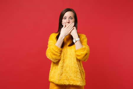 Portrait of shocked scared young woman in yellow fur sweater covering mouth with hands isolated on bright red wall background in studio. People sincere emotions, lifestyle concept. Mock up copy space
