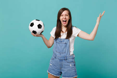 Crazy screaming girl football fan cheer up support favorite team with soccer ball spreading hand isolated on blue turquoise background. People emotion sport family leisure concept. Mock up copy space Stockfoto