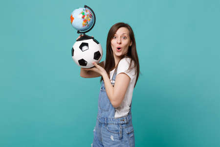 Excited happy woman football fan support favorite team with soccer ball, world globe isolated on blue turquoise background. People emotions, sport family leisure lifestyle concept. Mock up copy space