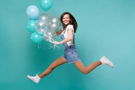 Portrait of happy cute young woman in denim clothes jumping high, celebrating and holding colorful air balloons isolated on blue turquoise background. Birthday holiday party, people emotions concept
