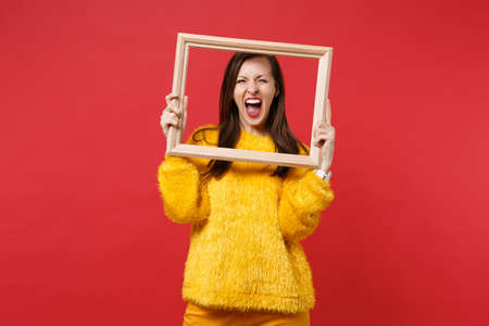 Portrait of crazy young woman in yellow fur sweater screaming, holding picture frame isolated on bright red wall background in studio. People sincere emotions, lifestyle concept. Mock up copy space