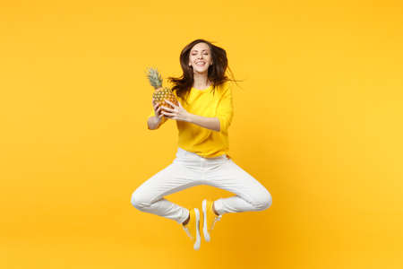Cute young woman in casual clothes keeping eyes clothes jumping hold fresh ripe pineapple fruit isolated on yellow orange background. People vivid lifestyle relax vacation concept. Mock up copy space