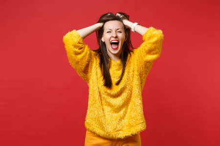 Portrait of crazy funny young woman in yellow fur sweater screaming, clinging to head isolated on bright red wall background in studio. People sincere emotions, lifestyle concept. Mock up copy space Фото со стока