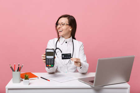 Female doctor sit at desk work on computer with medical document credit card in hospital isolated on pastel pink background. Woman in medical gown glasses stethoscope. Healthcare medicine concept 写真素材