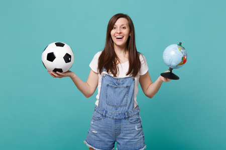Joyful woman football fan cheer up support favorite team with soccer ball, Earth world globe isolated on blue turquoise background. People emotions, sport family leisure concept. Mock up copy space Imagens