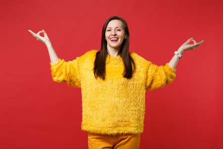 Smiling young woman in yellow fur sweater holding hands in yoga gesture, relaxing meditating isolated on red wall background in studio. People sincere emotions, lifestyle concept. Mock up copy space 写真素材
