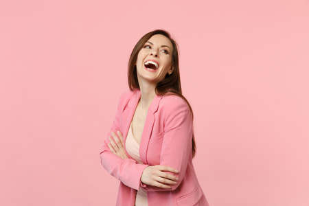 Portrait of cheerful laughing young woman in jacket standing, holding hands folded isolated on pastel pink wall background in studio. People sincere emotions, lifestyle concept. Mock up copy space Imagens