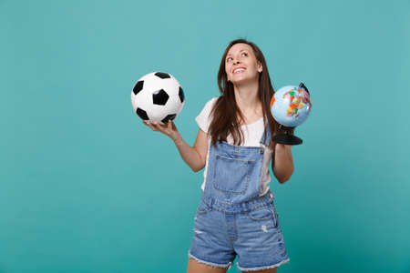 Dreamful woman football fan cheer up support favorite team with soccer ball, Earth world globe isolated on blue turquoise background. People emotions, sport family leisure concept. Mock up copy space Imagens