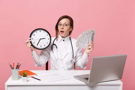 Female doctor sit at desk work on computer with medical document hold money in hospital isolated on pastel pink wall background. Woman in medical gown glasses stethoscope. Healthcare medicine concept Banque d'images - 119328304