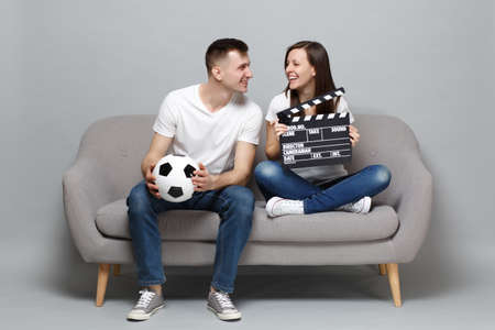Smiling couple woman man football fans cheer up support favorite team with soccer ball holding classic black film making clapperboard isolated on grey background. People emotions sport family concept