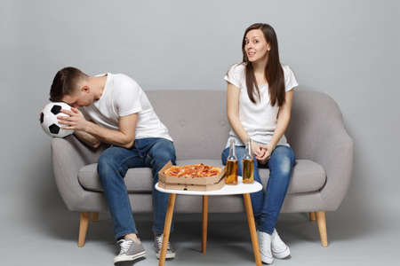 Couple woman boring man football fans in white t-shirt cheer up support favorite team with soccer ball, sitting isolated on grey background. People emotions, sport family leisure lifestyle concept Stock Photo