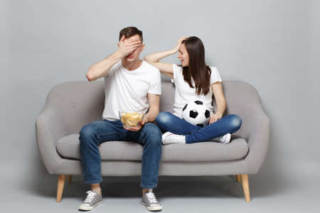 Displeased couple woman man football fans cheer up support favorite team with soccer ball, holding bowl of chips, covering face with palm isolated on grey background. Sport family lifestyle concept