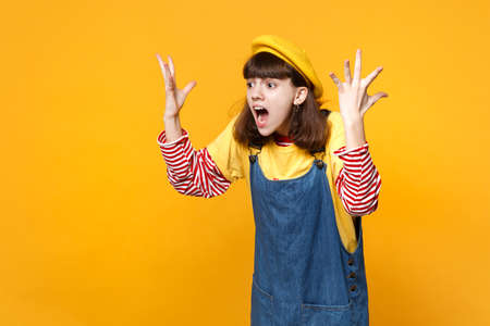 Irritated screaming girl teenager in french beret, denim sundress spreading, rising hands, swearing isolated on yellow wall background. People sincere emotions, lifestyle concept. Mock up copy space